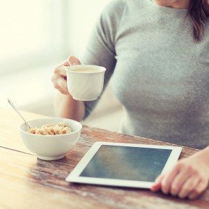 health, technology, internet, food and home concept - close up of woman drinking coffee and using tablet pc computer