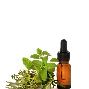 Herb leaf selection with an aromatherapy essential oil dropper bottle over white background.